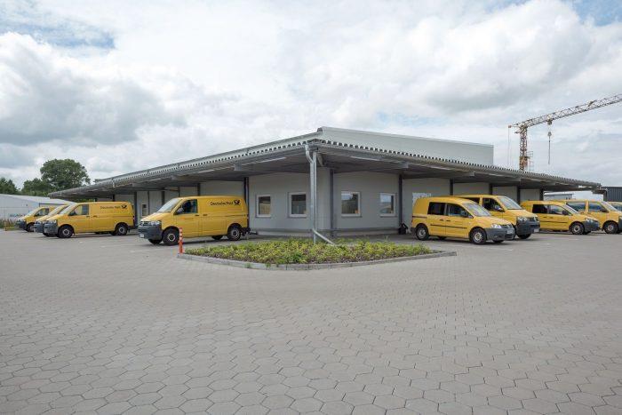 Gelbe Transporter vor Industriebau für DHL und Deutsche Post