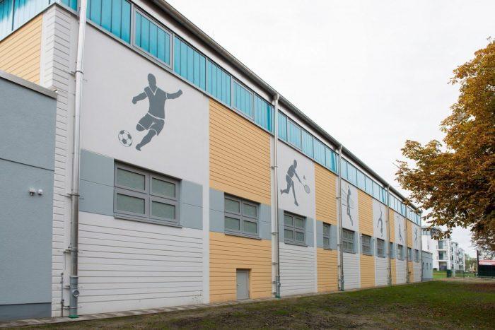 Sporthallenrückseite mit gelben und weißen Wandplatten in Warnemünde