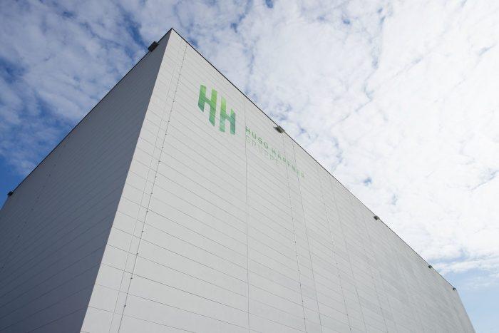 Gewerbebau mit weißen Wandplatten und grünem Hugo Häffner Logo