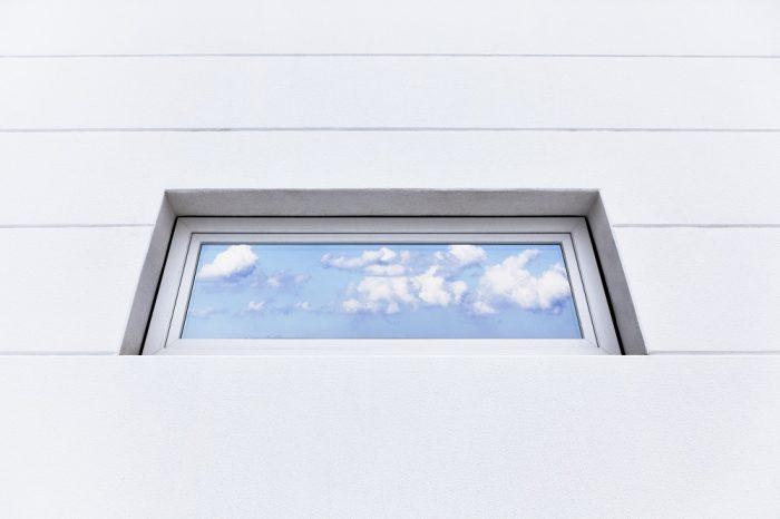 Fenster mit Himmelspiegelung und weißen Wandplatten