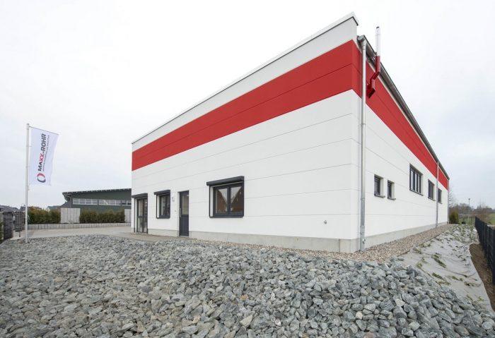 Seitenansicht Hallenbau Maxx-Rohr mit roten und weißen Wandplatten