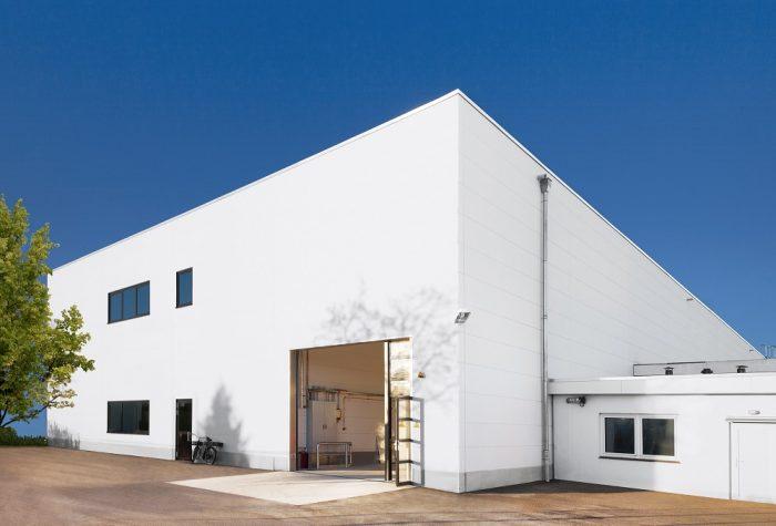 Weißer Lagerhallenbau mit Tor von Vosschemie