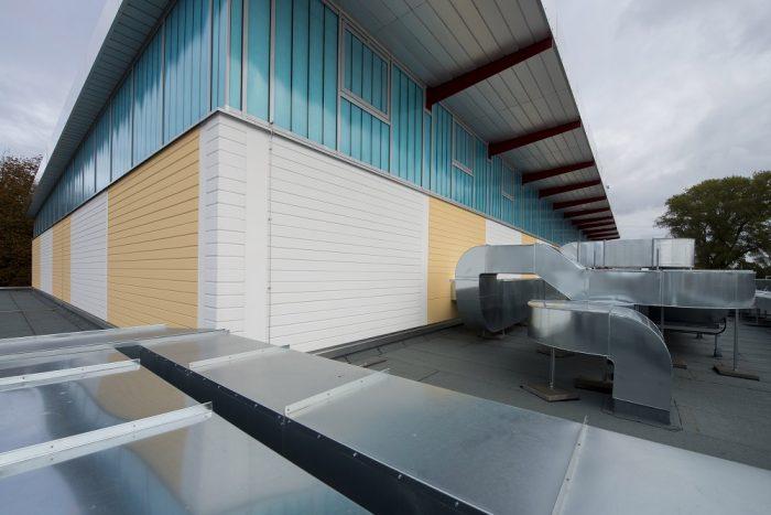 Sporthalle mit weißen und gelben Wandplatten und Luftkanälen in Warnemünde