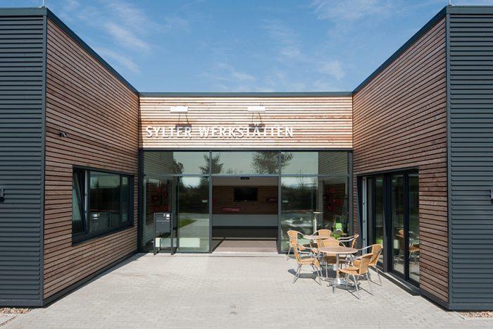 Eingang Sylter Werkstätten mit Holz und schwarzen Wandplatten