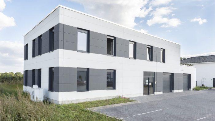 eletek Gewerbebau mit schwarzen und weißen Dachplatten